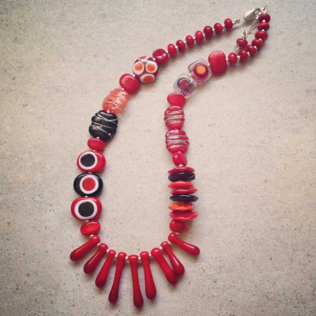 Gorgeous red necklace with a splash of orange and black!  handmade glass beads by Julie Frahm
