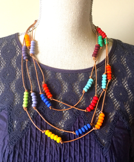 Colour wheel necklace with etched beads on leather (modelled)