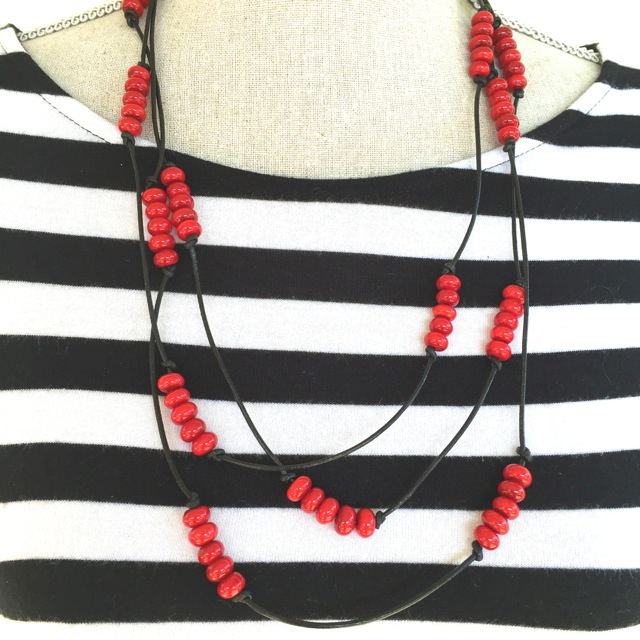 Handmade red glass beads on black leather
