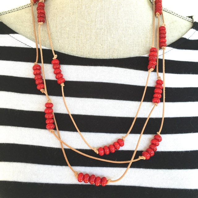 Handmade red glass beads on brown leather