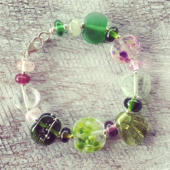 Recycled glass flower bracelet | beads made from assorted wine bottles and other broken glass objects.